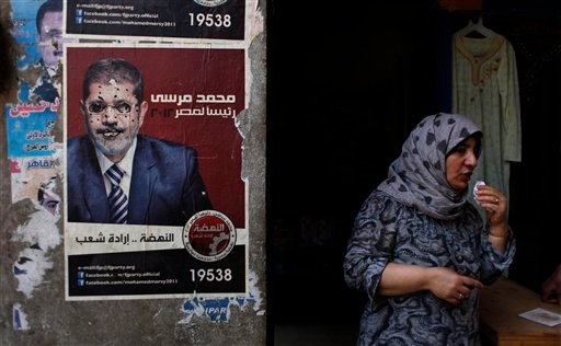 """An Egyptian female vendor stands at her shop next to a poster with a defaced pictures of presidential candidate Mohammed Morsi and Arabic that reads """"Mohammed Morsi, president for Egypt, revival is the will of the people,"""" in Cairo, Egypt June 20, 2012."""