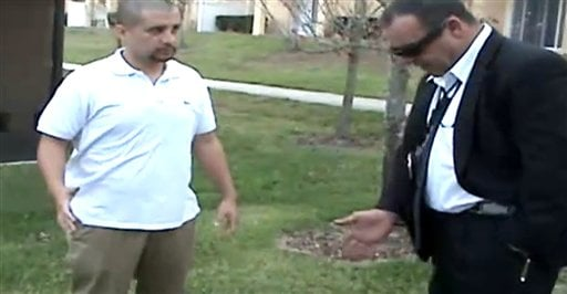 In this Feb. 27, 2012 image taken from a Sanford Police video posted on a website called gzlegalcase.com by George Zimmerman's defense team, Zimmerman speaks to an unidentified investigator at the scene of Trayvon Martin's fatal shooting. (AP Photo)