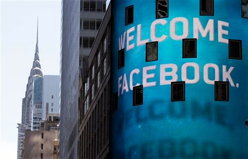 FILE- In this Friday, May 18, 2012, file photo, the animated facade of the Nasdaq MarketSite, welcomes the Facebook IPO, in New York's Times Square. (AP Photo/Richard Drew, File)