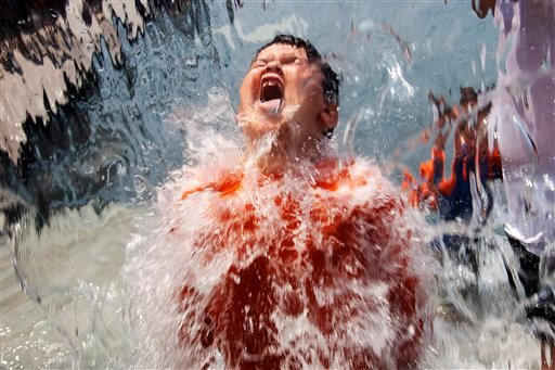 Lucas Olivo, 6, of Cheverly, Md., opens his mouth wide while running through a wall of water at Yards Park in Washington, on Thursday, June 21, 2012. (AP Photo/Jacquelyn Martin)