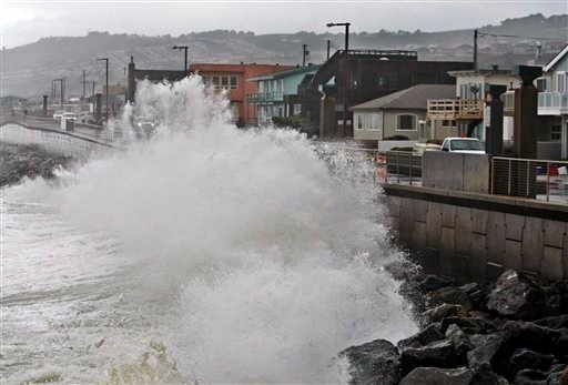File - In this Jan. 20, 2010 file photo, waves pound a wall near buildings in Pacifica, Calif., during a rain storm. A new federal report gives the West Coast its best look yet at what to expect from rising sea levels due to climate change. (AP Photo)