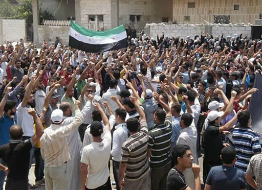 This citizen journalism image provided by Shaam News Network SNN, purports to show anti-Syrian regime protesters raise up their hands and shout slogans as they wave the Syrian revolutionary flag, During a demonstration in central Daraa, southern Syria.