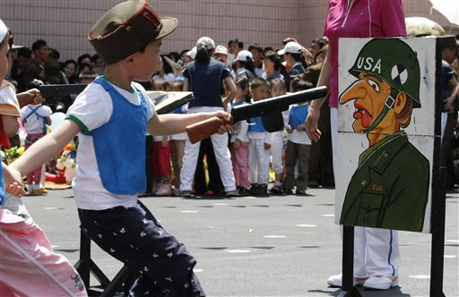 In this June 1, 2012 file photo, a child points a toy gun at a painting of a U.S. soldier during a game for children on the grounds of Kyongsang Kindergarten in Pyongyang, North Korea. (AP Photo/Kim Kwang Hyon, File)