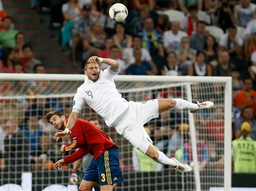 France's Olivier Giroud falls over Spain's Gerard Pique during the Euro 2012 soccer championship quarterfinal match between Spain and France in Donetsk, Ukraine, Saturday, June 23, 2012. (AP Photo/Laurent Cipriani)