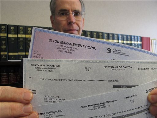 In this Monday, June 11, 2012 photo, Assistant Attorney General David Kirkman holds checks of the type often received by targets in his Raleigh, N.C., office.