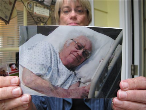 In this Monday, June 18, 2012 photo at her Cary, N.C., home, Donna Parker holds a picture of her father, Charles, shortly before his death in February 2012.