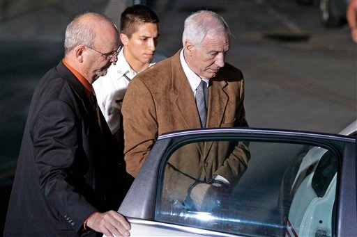 Former Penn State University assistant football coach Jerry Sandusky, right, is escorted by Centre County Sheriff Denny Nau, left, as he is taken into custody at the Centre County Courthouse after being found guilty of multiple charges. (AP Photo)