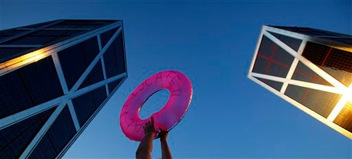 FILE-In this June 16, 2012, file photo, a demonstrator holds a life saver in front of the headquarters of Bankia bank during a protest against the Spanish bank in Madrid, Spain. (AP Photo/Andres Kudacki)