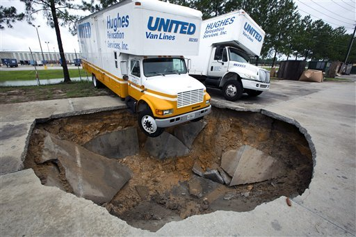 A truck hangs over the edge of a sinkhole that opened up in the parking lot of Hughes Relocation Services, Monday, June 25, 2012, in Salt Springs, Fla. (AP Photo/The Ocala Star-Banner, Alan Youngblood)