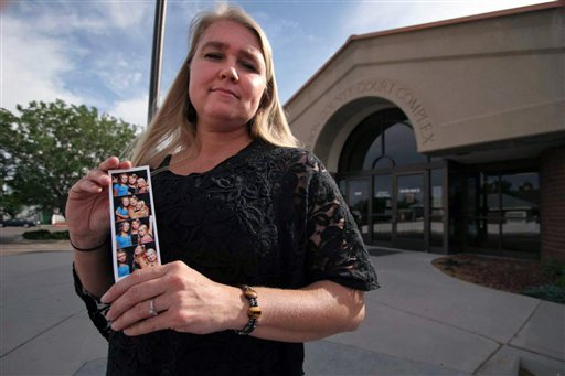 In this June 6, 2012, photo, Valerie Bruno holds a photo of her three daughters as she poses for a photo outside the Carbon County Court Complex in Price, Utah.