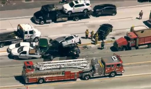 This image made from video provided by KABC-TV shows fire officials working on a freeway pileup in northern Los Angeles County involving at least 19 vehicles that has injured at least 15 people, two of them critically. (AP Photo/KABC-TV)