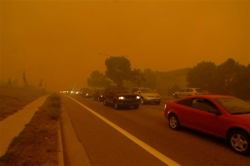 People flee the Waldo Canyon Fire with little time to spare as the fire burns through neighborhoods west of Colorado Springs, Colo. on Tuesday, June 26, 2012. (AP Photo/Bryan Oller)