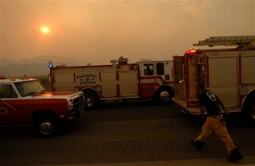 Firefighters get ready to head into neighborhoods which were caught by the Waldo Canyon Fire after it swept down into western portions of Colorado Springs, Colo. on Tuesday, June 26, 2012. (AP Photo/Bryan Oller)