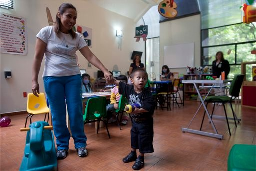 Jesus Rodriguez, 2, holds onto the hand of his mother Maria Fernandez, in a play area of La Raza Medical Center, in Mexico City, Tuesday, June 26, 2012. (AP Photo/Esteban Felix)