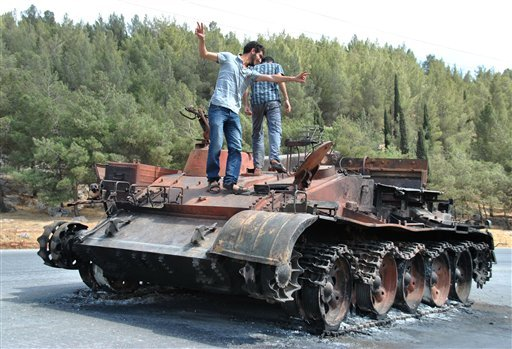 In this picture taken on Saturday, June 23, 2012, a Syrian man flashes the victory sign as he stands with his friend atop of a burned Syrian military tank which was destroyed during a clashes between Syrian forces and rebels. (AP Photo/Fadi Zaidan)