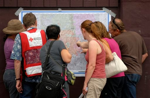 Evacuees of the Waldo Canyon Fire look at the most recent map of the fire's progression at the Cheyenne Mountain High School evacuation center on Wednesday, June 27, 2012, in Colorado Springs, Colo. (AP Photo/Bryan Oller)