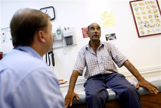 Luis Gutierrez, right, talks with Dr. Javier Hiriart at Camillus Health Concern, Wednesday, June 27, 2012, in Miami. Camillus is a private, non-profit organization that provides health care to the homeless and poor in Miami. (AP Photo/Lynne Sladky)