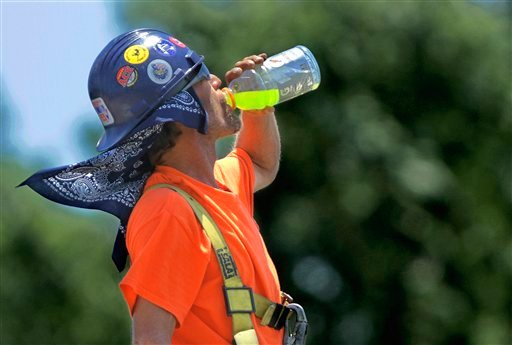 A construction worker takes a break to keep cool and hydrated as record breaking heat moves across the country Wednesday, June 27, 2012 in Springfield, Ill. (AP Photo/Seth Perlman)