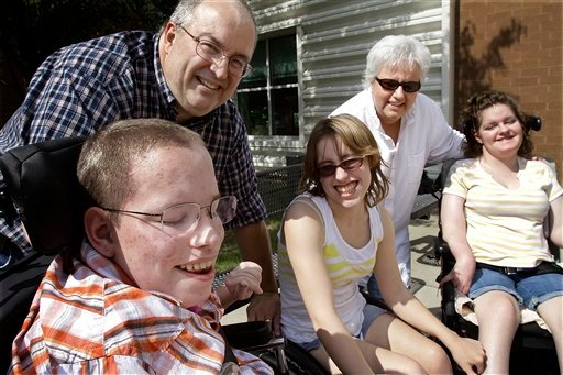 FILE - In this Setp. 22, 2010, file photo Jerry and Becky Morefield enjoy some time together with their 15-year-old triplets with cerebral palsy in Mahomet, Ill. (AP Photo/Seth Perlman, File)