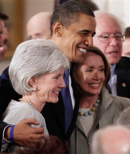 File/March 23, 2010: President Barack Obama embraces Health and Human Services Secretary Kathleen Sebelius, left, and House Speaker Nancy Pelosi of Calif. in the East Room of the White House after he signed the health care bill.(AP Photo/Charles Dharapak)