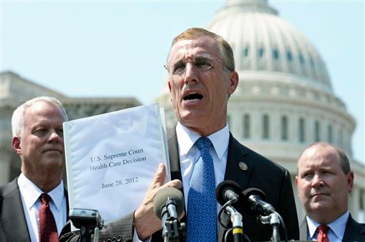 FILE - In this Thursday, June 28, 2012 file photo, Rep. Tim Murphy, R-Pa., center, holds up a copy of the Supreme Court's health care ruling during a news conference by the GOP Doctors Caucus on Capitol Hill in Washington. (AP Photo/Cliff Owen)