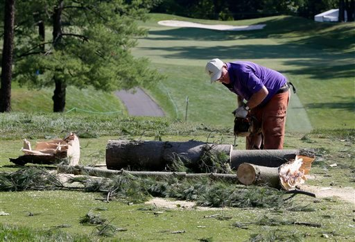 A worker chainsaws a tree that fell onto a tee box on the the 12th hole at Congressional Country Club in Bethesda, Md., Saturday, June 30, 2012, after a strong storm blew through overnight. (AP Photo/Patrick Semansky)