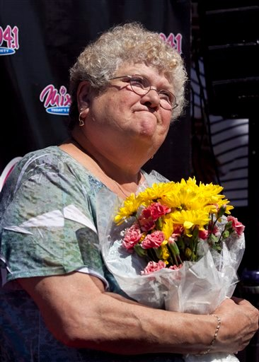 In this June 28, 2012 file photo, bus monitor Karen Klein, of Greece, N.Y., holds flowers during an award ceremony in her honor at a radio station. (AP Photo/Steven Senne, File)