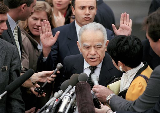 In this Nov. 22, 1991 file photo, an aide to Israeli Prime Minister Yitzhak Shamir asks reporters to back off as Shamir leaves a meeting with President Bush White House. (AP Photo/Barry Thumma, File)