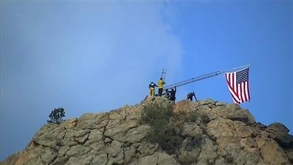This Sunday, July 1, 2012 video image taken from AP video shows a group of firefighters raising an American flag above a section of the burned out neighborhood, Mountain Shadows, Colo. (AP Photo/AP Video, C.J. Moore)