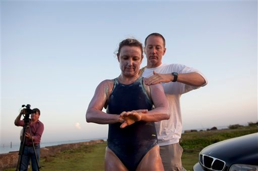 British-Australian swimmer Penny Palfrey and her husband Chris rub creme on her body in preparation for her bid to complete a record swim from Cuba to Florida, in Havana, Cuba, Friday, June 29, 2012. (AP Photo/Ramon Espinosa)