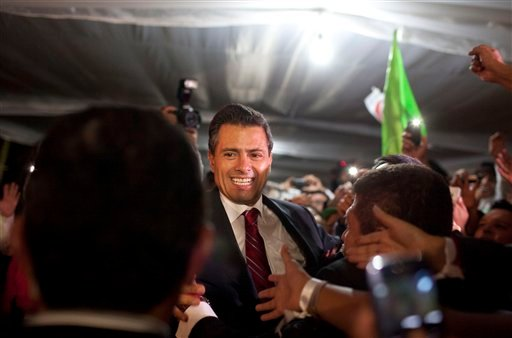 Enrique Pena Nieto, presidential candidate for the Revolutionary Institutional Party (PRI), greets supporters at his party's headquarters in Mexico City, early Monday, July 2, 2012.  (AP Photo/Alexandre Meneghini)