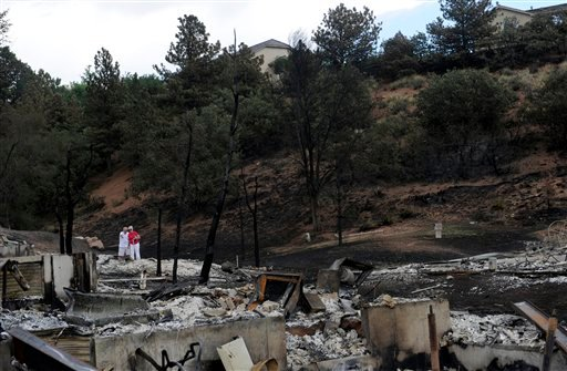 Jerry Lidenberg, 75, and his wife Beth , 71, look over the ashes of the home they lived in for 19 years on Sunday, July 1, 2012, in the Mountain Shadows subdivision of Colorado Springs. (AP Photo/The Denver Post, Heather Rousseau)