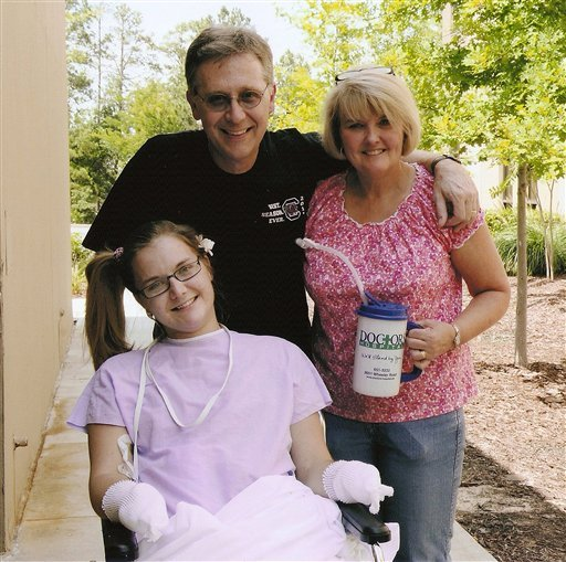 FILE - In this Saturday, June 23 2012 file photo provided by the Copeland family, Aimee Copeland, left, poses with her parents, Andy and Donna Copeland, outside Doctors Hospital in Augusta, Ga.