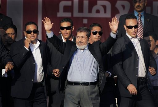 FILE - In this Friday, June 29, 2012 file photo, Egypt's new President-elect Mohammed Morsi waves to supporters at Tahrir Square, the focal point of Egyptian uprising, in Cairo, Egypt. (AP Photo/Amr Nabil, File)