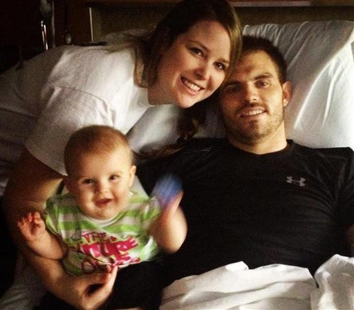 In an undated photo provided by the Mills family, Travis Mills is seen in his hospital bed with his wife Kelsey and daughter Chloe at the Walter Reed National Military Medical Center in Bethesda, Md. (AP Photo/Mills Family)