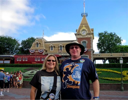 In this Sunday, July 1, 2012, photo, Jeff Reitz and Tonya Mickesh pose for a picture at the halfway point, day 183, in their mission to visit Disneyland in Anaheim, Calif., every day this year.