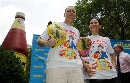 "Five-time hot dog-eating world champion Joey Chestnut, left, and women's record-holder Sonya ""The Black Widow"" Thomas, pose for photographers following a weigh-in for contestants. (AP Photo/Kathy Willens)"