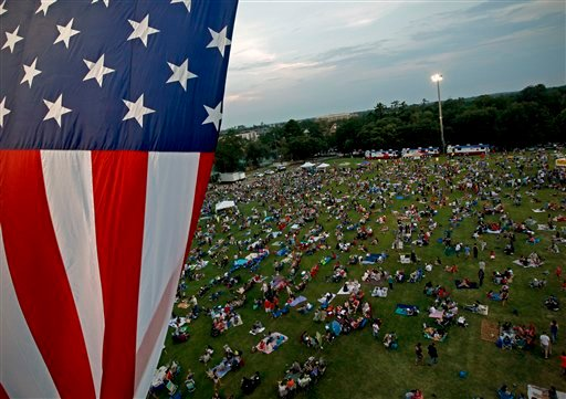 A United States flag flies over a field during the Fanfare and Fireworks celebration at the University of Florida on Tuesday, July 3, 2012, in Gainesville, Fla. (AP Photo/The Gainesville Sun, Matt Stamey)