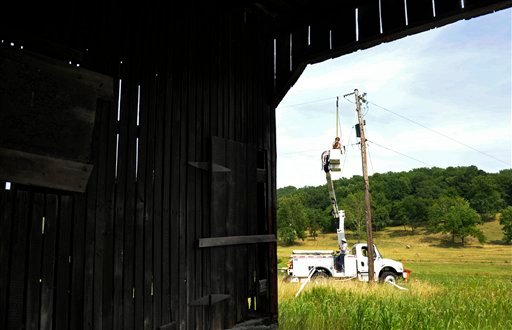 A Gulf Power lineman works to restore a power line near a barn in Middleburg, Va., Tuesday, July 3, 2012. Severe storms swept through the area leaving many without electricity. (AP Photo/Cliff Owen)