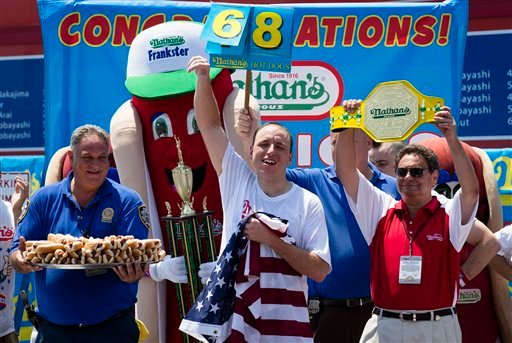 Five-time reigning champion Joey Chestnut celebrates after he wins his sixth straight Coney Island hot dog eating contest on Wednesday, July 4, 2012 at Coney Island, in the Brooklyn borough of New York. (AP Photo/John Minchillo)