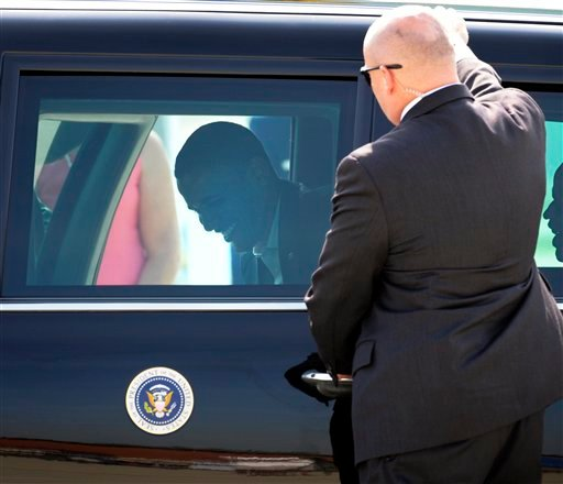 President Barack Obama exits his limousine while a Secret Service agent stands guard at the door, before boarding Air Force One at Andrews Air Force Base, Md., Thursday, July 5, 2012. (AP Photo/Cliff Owen)