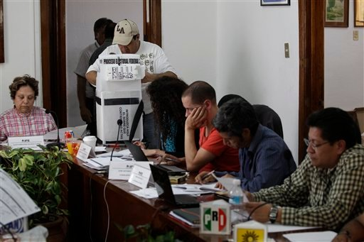 Election officials and party representatives begin the computation of ballot boxes at an electoral institute district council in Mexico City, Wednesday July 4, 2012. (AP Photo/Dario Lopez-Mills)