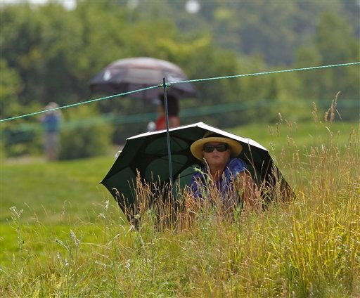 Fans use large umbrellas to get some respite from the heat on the 13th hole during the first round of the U.S. Women's Open golf tournament, Thursday, July 5, 2012, in Kohler, Wis. (AP Photo/Jeffrey Phelps)