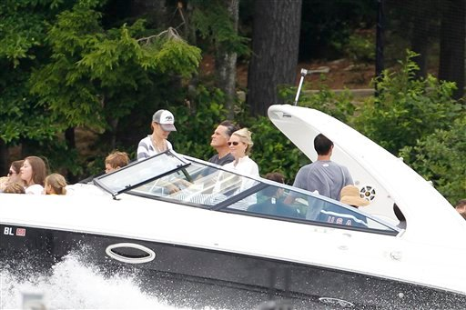 Republican presidential candidate, former Massachusetts Gov. Mitt Romney, seen at center next to his wife Ann, drives his boat out of his vacation home with his grandchildren seated on the bow on Lake Winnipesaukee in Wolfeboro, N.H.