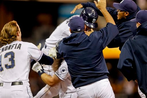 San Diego Padres' Everth Cabrera is mobbed by teammates after his game winning hit in the bottom of the ninth inning gave the Padres a 2-1 victory over the Cincinnati Reds during a baseball game Thursday, July 5, 2012 in San Diego.