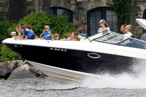 In this July 5, 2012, photo Republican presidential candidate Mitt Romney, at right next to his wife Ann, drives his boat out of his vacation home with his grandchildren seated on the bow on Lake Winnipesaukee N.H. (AP Photo/Charles Dharapak, file)