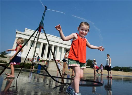Sophie, 3, from Connecticut, frolics with a water sprinkler set up at the National Mall near the Lincoln Memorial, rear, in Washington Saturday, July 7, 2012.