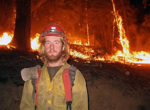 This July 2008 photo provided by John Lauer shows firefighter John Lauer in front of a back burn during a wildfire in Montana. (AP Photo/Courtesy John Lauer)