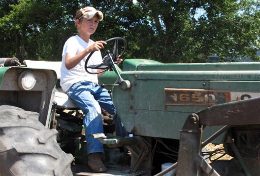 In a June 20, 2012, photo ten-year-old Jacob Mosbacher guides a tractor through a bean field on his grandparents' property near Fults, Ill. (AP Photo/Jim Suhr)