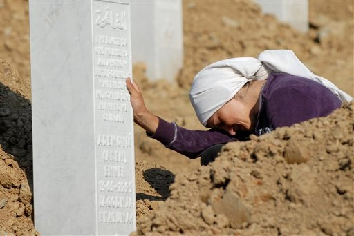 A woman weeps near the grave of her relative among the graves of Srebrenica victims at the Memorial Cemetery. Thousands gathered in the cemetery for the mass burial of 520 bodies, marking the 17th anniversary of the massacre. (AP Photo/Sulejman Omerbasic)